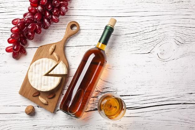 Butelka białego wina, winogron, sera i kieliszek do wina na białej drewnianej desce. widok z góry z miejsca na kopię.