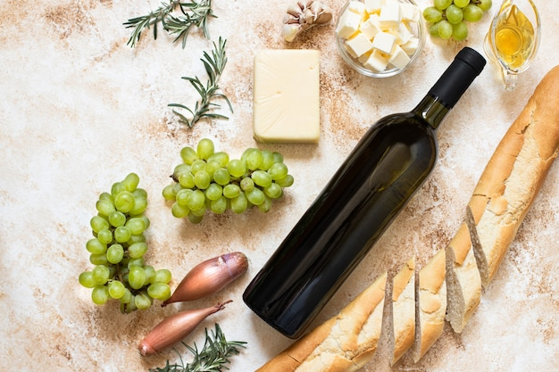 Butelka białego wina, winogron, sera, masła i bagietki z widokiem z góry