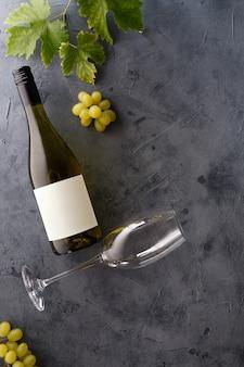 Butelka białego wina z etykietą. kieliszek wina i winogron. makieta butelki wina.