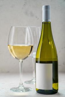 Butelka białego wina z pustą etykietą i okularami, makieta projekt logo
