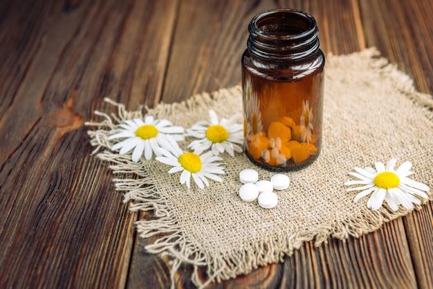 Butelka białych tabletek ziołowych i kwiatów rumianku na ciemnym drewnie, lek homeopatyczny.