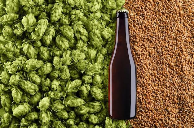 Butelka ciemnego piwa na tle z chmielem i pszenicą makieta gotowa do projektowania
