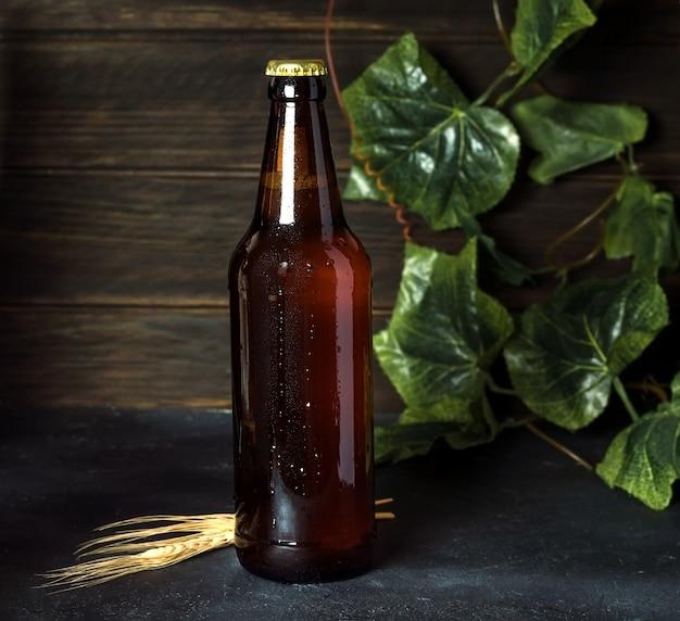 Butelka ciemnego świeżego piwa na ciemnym drewnianym