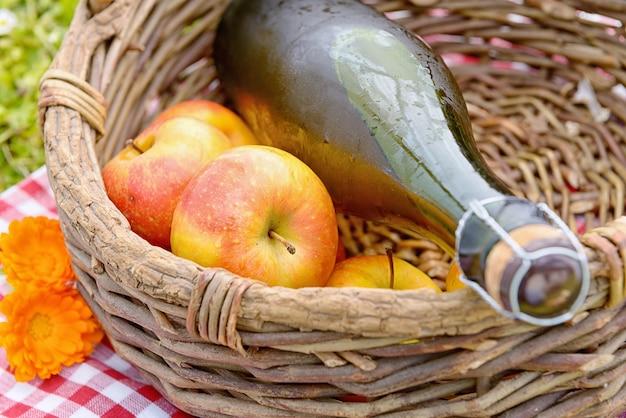 Butelka cydru z jabłkami w koszu