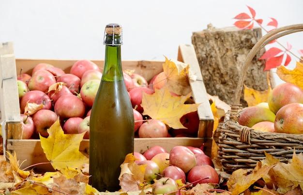Butelka cydru z normandii z wieloma jabłkami