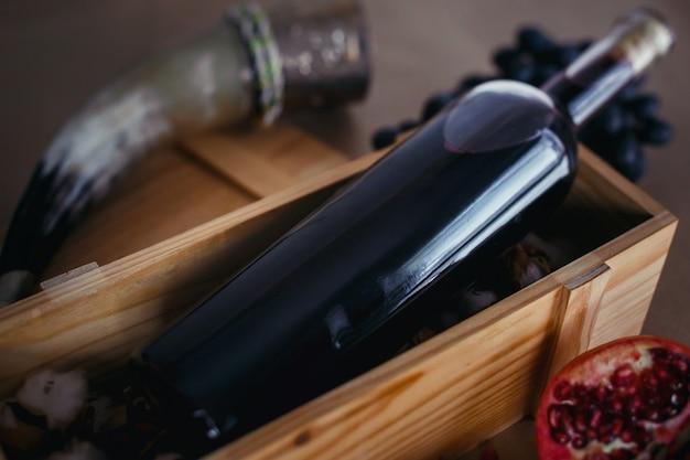 Butelka czerwonego wina gronowego w drewnianym pudełku. w pobliżu znajdują się granaty, czarne winogrona i róg do picia