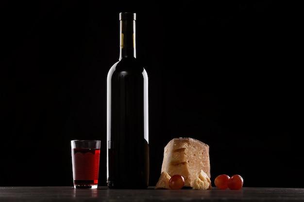 Butelka czerwonego wina i kieliszek czerwonego wina, drogi rodzaj sera z pleśnią i winogronami. na czarnym tle. miejsce na logo.