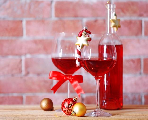 Butelka czerwonego wina i kieliszki z prezentami świątecznymi na powierzchni ściany