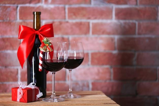 Butelka czerwonego wina i kieliszki z prezentami świątecznymi na ścianie