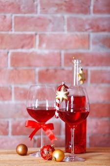 Butelka czerwonego wina i kieliszki z prezentami świątecznymi na tle ściany