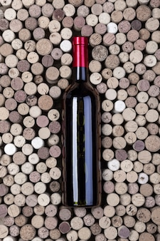 Butelka czerwonego wina i korki na drewnianym stole