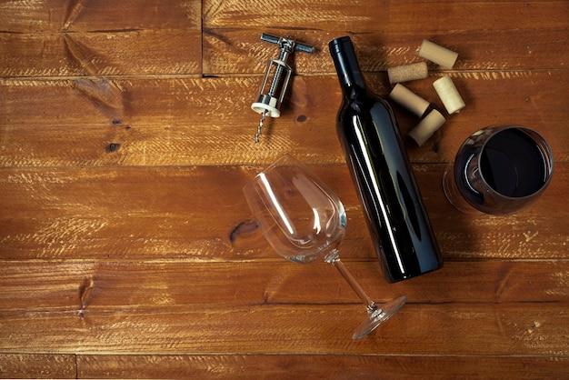 Butelka czerwonego wina i szklanki z korkociągiem