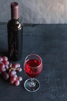 Butelka czerwonego wina i wina z winogronami na czarnej powierzchni