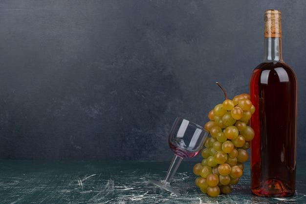 Butelka czerwonego wina i winogrona na marmurowym stole