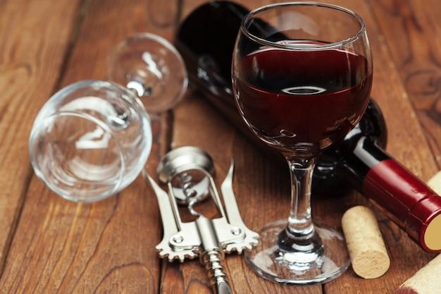Butelka czerwonego wina, kieliszek do wina i korkociąg na drewnianym stole tło