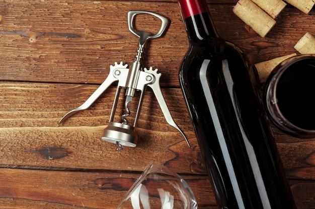 Butelka czerwonego wina, kieliszek do wina i korkociąg