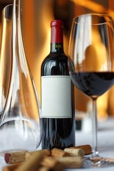 Butelka czerwonego wina, kieliszek wina i karafka na stole z białym obrusem.