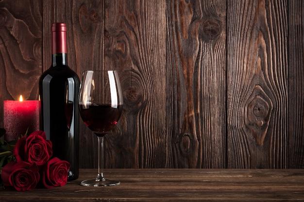 Butelka czerwonego wina, kieliszek wina, świeca i róże na drewnianym tle