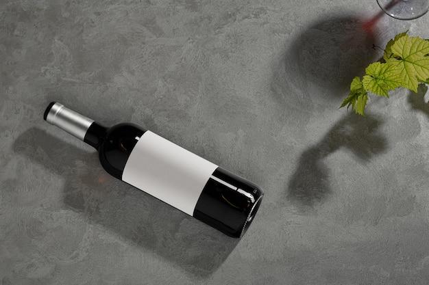 Butelka czerwonego wina z etykietą. kieliszek wina i winogron. makieta butelki wina. widok z góry.