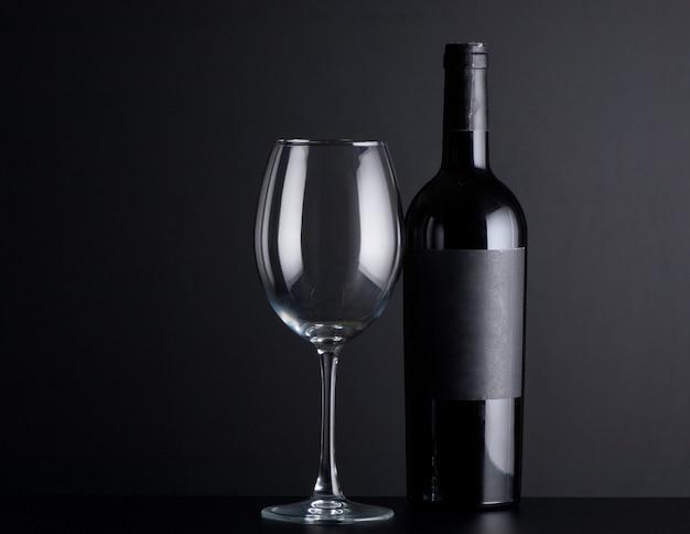 Butelka czerwonego wina z kieliszkiem na czarnym tle