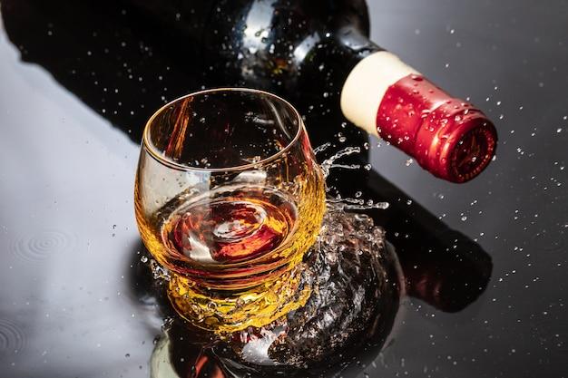Butelka czerwonego wina z lampką. plusk wody i kropla na czarnym odbiciu.