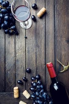 Butelka czerwonego wina ze szkła i winogron na drewnianym