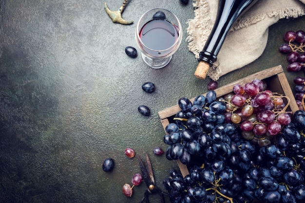 Butelka czerwonego wina ze szkłem i winogronami na ciemnym kamieniu