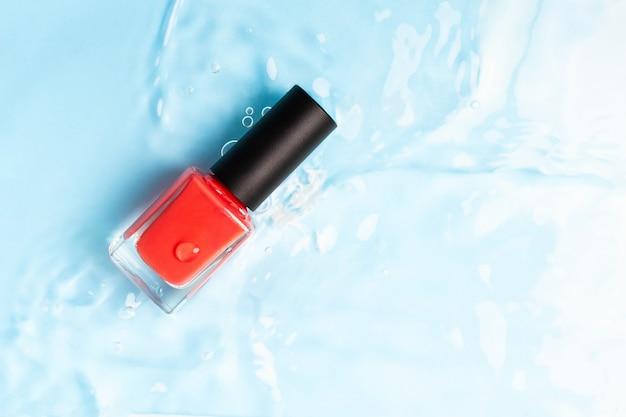 Butelka czerwony kolorowy lakier do paznokci na tle niebieskiej wody. widok z góry. skopiuj miejsce