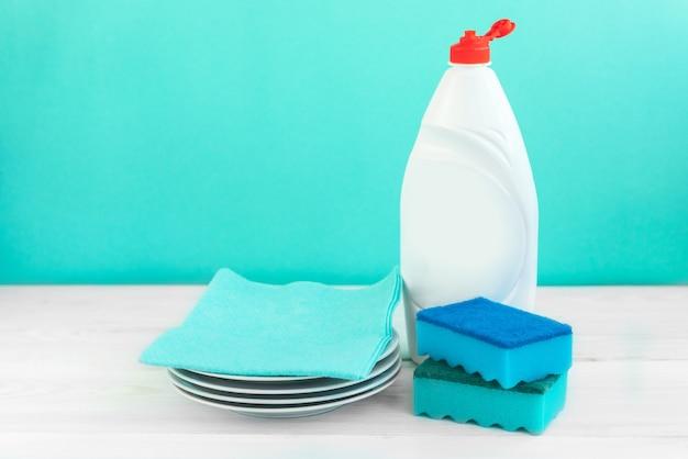 Butelka do mycia naczyń, gąbki, naczynia na białym drewnianym stole na zielonej ścianie