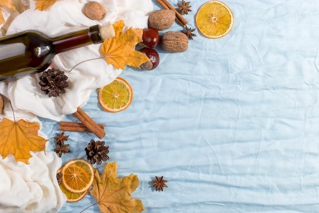 Butelka grzanego wina z przyprawami, szalikiem, suchymi liśćmi i pomarańczami na stole. jesienny nastrój, metoda na ogrzanie się na zimno, copyspace.