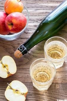 Butelka i dwie szklanki cydru na drewnianym stole