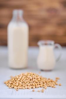 Butelka i dzban mleka sojowego na białym stole