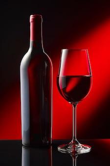 Butelka i kieliszek czerwonego wina stoją na czarnym lustrzanym stole.