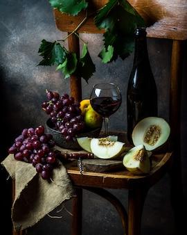Butelka i kieliszek czerwonego wina, winogron i korka na krześle. melon, kawałek melona. różowe winogrono, gruszka. martwa natura z jedzeniem. fotografia ciemnych potraw. koncepcja jesień. alkohol, uprawa winorośli.
