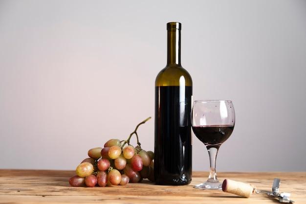 Butelka i kieliszek czerwonego wina z dojrzałymi winogronami