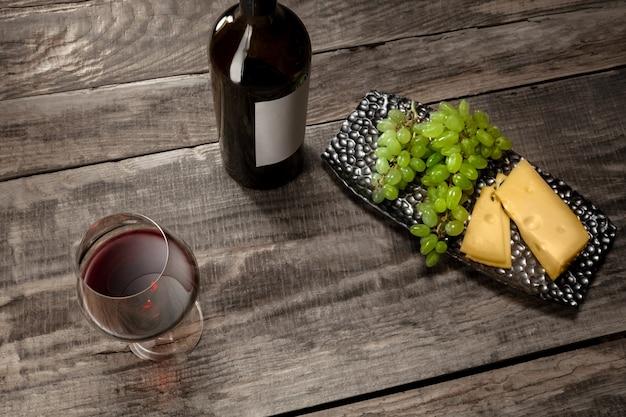 Butelka i kieliszek czerwonego wina z owocami na drewnianym tle