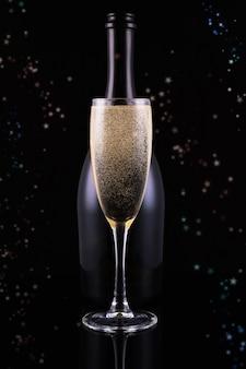 Butelka i kieliszek szampana ze złotymi kółkami bokeh. miejsce na tekst. świąteczna koncepcja.