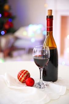 Butelka i kieliszek wina z świątecznym wystrojem