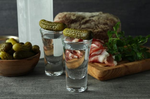 Butelka i kieliszki wódki i różne przekąski na szarym stole