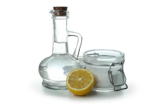 Butelka i słoik kwasu i cytryny na białym tle na białym tle