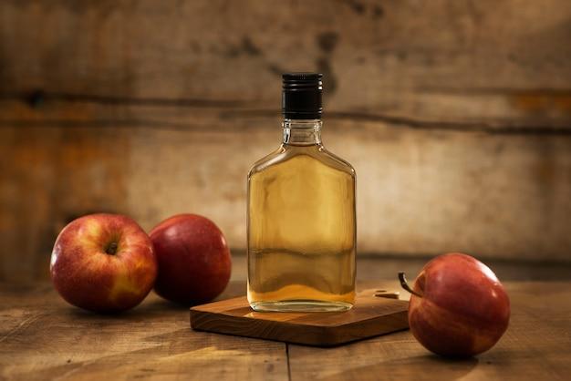 Butelka i szklanka naturalnego soku jabłkowego oraz kawałki jabłka