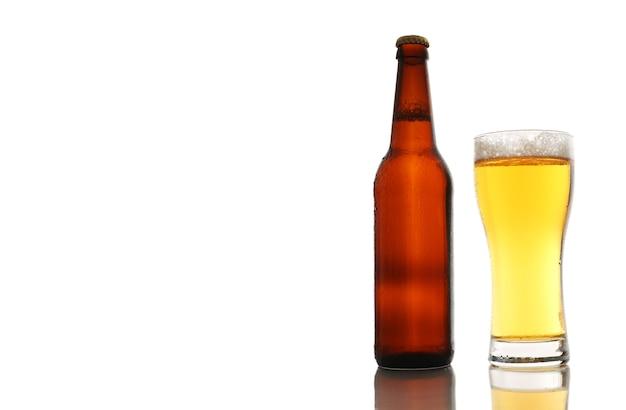 Butelka i szklanka piwa z pianką na białym tle