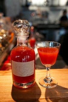 Butelka i szkło wypełnione czerwonym napojem alkoholowym na blacie barowym
