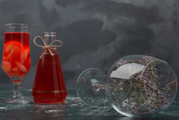 Butelka i szkło z sokiem i szkłem z kwiatem.