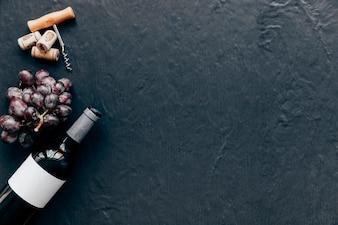 Butelka i winogron w pobliżu korkociąg i korki