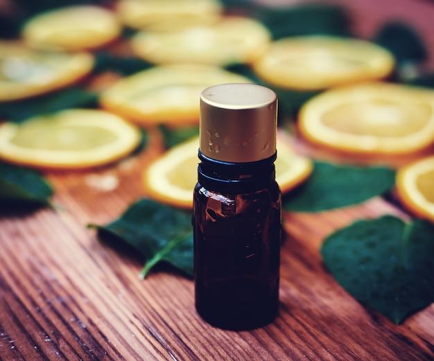 Butelka istotny olej z pomarańcz na drewnianym tle - medycyna alternatywna