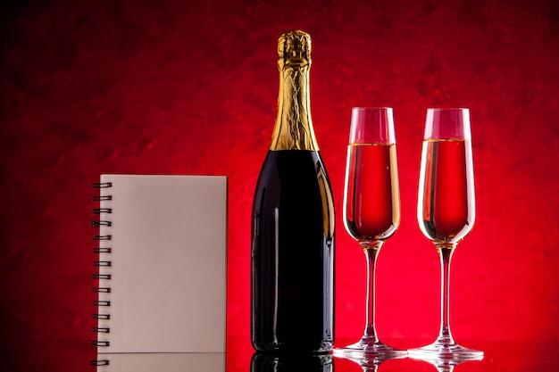 Butelka kieliszków do wina i notatnik z widokiem z przodu