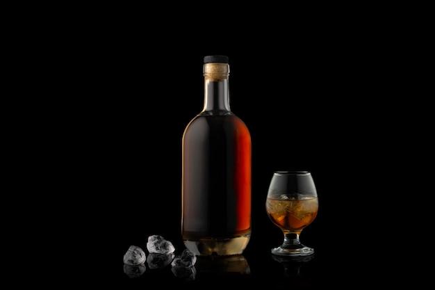 Butelka koniaku, szklanka i trzy kawałki lodu na czarnym.