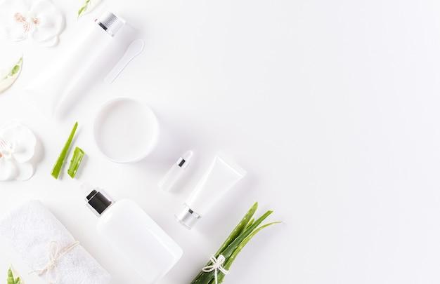 Butelka kosmetyczna, krem do skóry z zielonymi liśćmi ziołowymi.