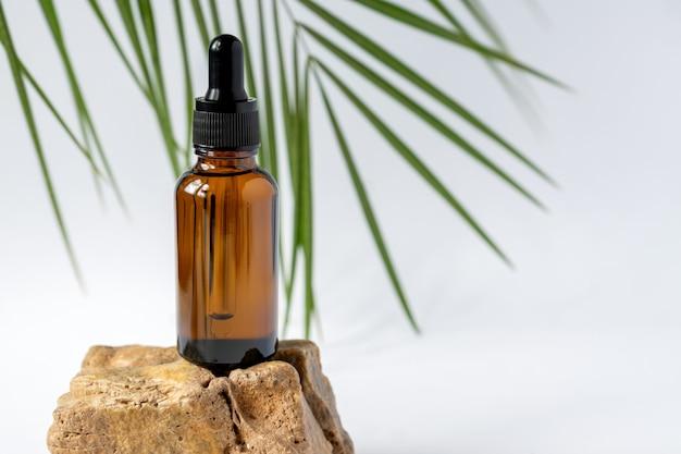 Butelka kosmetyczna z ciemnego szkła z zakraplaczem na szarej powierzchni z kamieniem i liściem palmowym